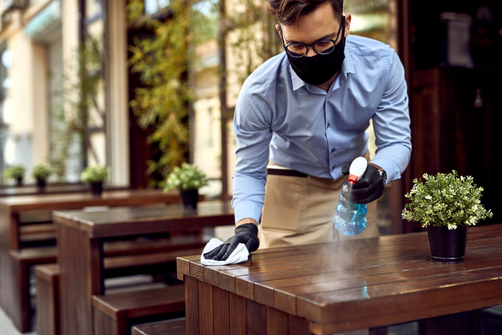 Man in mask cleaning tables - Restaurant Insurance, Hull